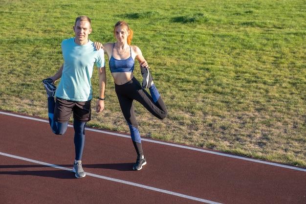 Junge paare von gesunden sportlern, jungen und mädchen, die aufwärmübungen machen, bevor sie auf roten spuren des öffentlichen stadions im freien laufen.