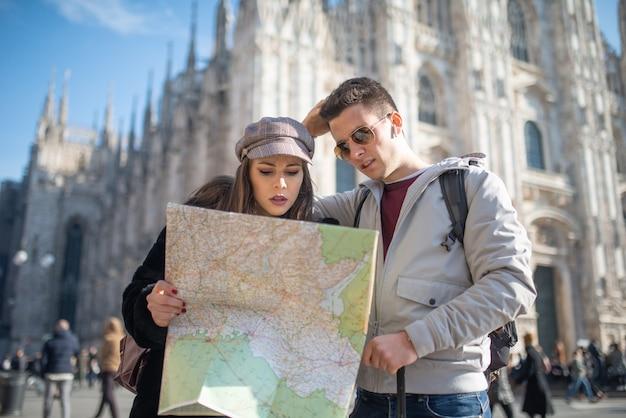 Junge paare von touristen, die eine karte in mailand, italien halten