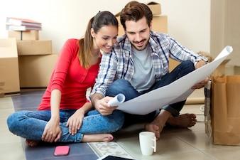 Junge Paare, welche die Pläne ihres neuen Hauses betrachten