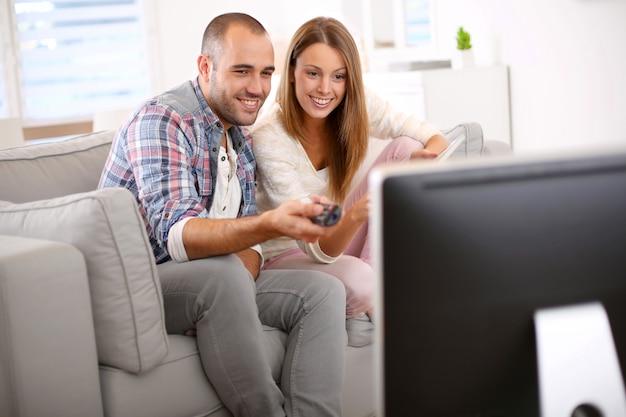 Junge paare zu hause, die nach fernsehprogramm suchen