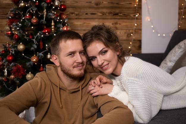 Junge paare zu hause zur weihnachtszeit nahe schön verziertem weihnachtsbaum
