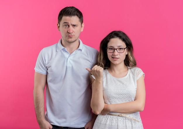 Junge paarfrau, die mit dem finger auf ihren verwirrten freund zeigt, der über rosa wand steht