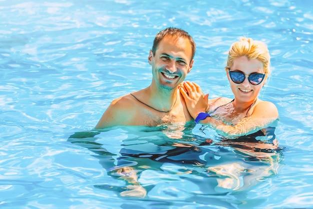 Junge paarmannfrau im swimmingpool, konzept der aktiven freizeit