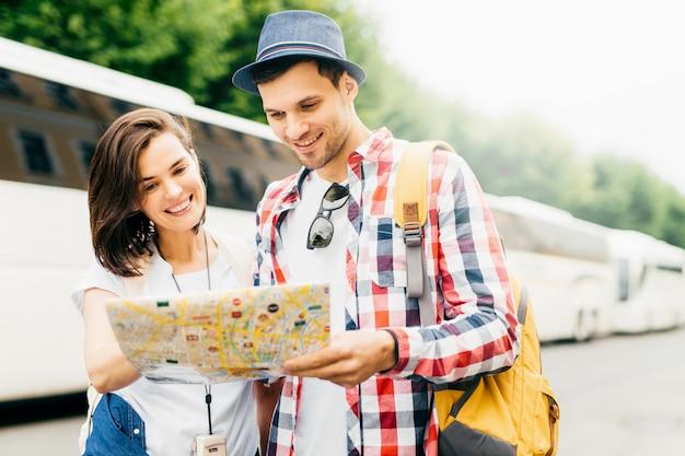 Junge paartouristen, die aufmerksam in der karte beim suchen nach museum in der großstadt schauen. stilvoller mann im hut und in kariertem hemd, die den rucksack, stehend nahe seiner frau und suchen nach neuem bestimmungsort halten