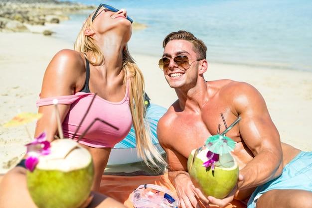 Junge paarurlauber, die kokosnusscocktail trinken und spaß am tropischen strand in phuket thailand haben
