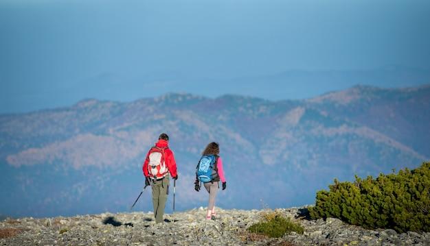 Junge paarwanderer mit rucksäcken zu fuß auf felsigen berg plato