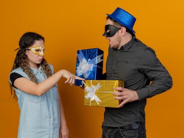 Junge partei coulpe, die maskerade-augenmaskenmädchen trägt, das finger auf geschenkbox in kerlhand lokalisiert auf orange setzt