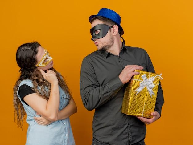 Junge parteipaare betrachten einander, der maskerade-augenmasken-kerl hält, der geschenkbox lokalisiert auf orange hält