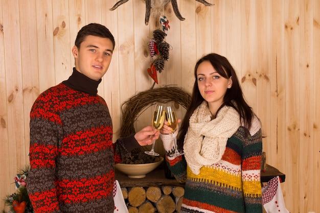Junge partner in lässigen winteroutfits werfen flötengläser mit champagner im haus, während sie in die kamera schauen.