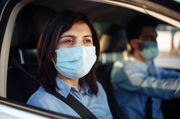 Junge passagierin nimmt eine fahrt mit dem taxi während der coronavirus-pandemie-quarantäne.