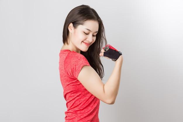 Junge passende asiatische frau, die handschuhe trägt, zeigen bizepsarm, glückliches gesundes sexy mädchen.