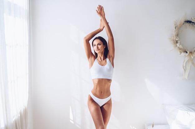 Junge passende frau in weißen dessous auf weißer wand lokalisiert. muskulöses schlankes attraktives weibchen mit flachem bauch. kopieren sie platz für text. körperpflege, gesundes und sportliches leben, haarentfernung, yoga-konzept