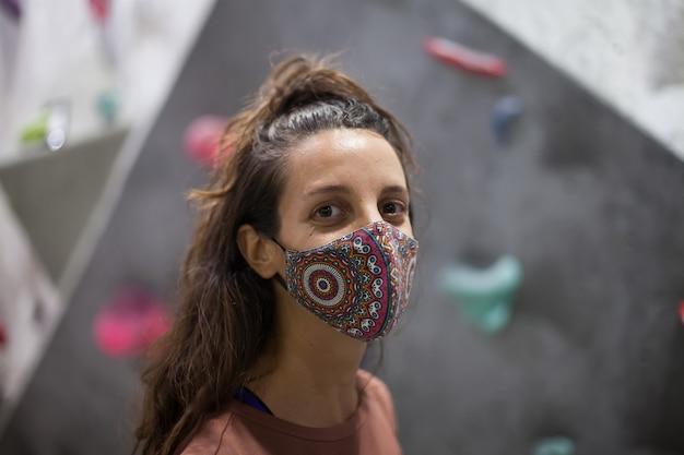 Junge passende frau kletterer tragen maske auf steilen felsen drinnen
