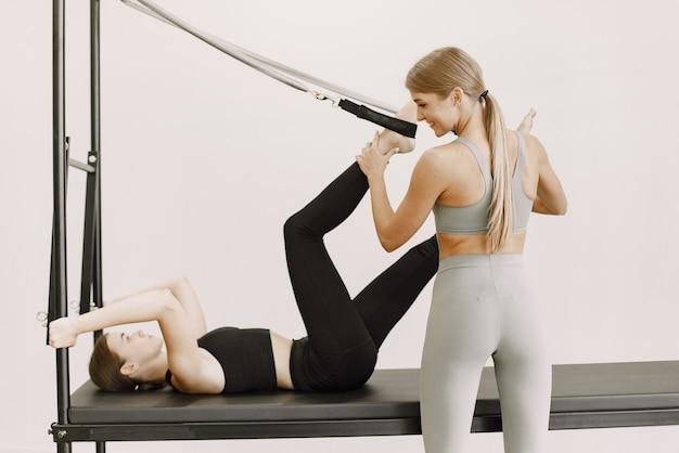 Junge passende frau mit einem weiblichen trainer im fitnessstudio. frau, die schwarze sportkleidung trägt. kaukasisches mädchen, das mit ausrüstung ausdehnt.