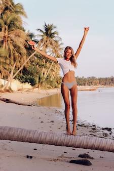 Junge passende frau mit wassermelone am tropischen strand bei sonnenuntergang