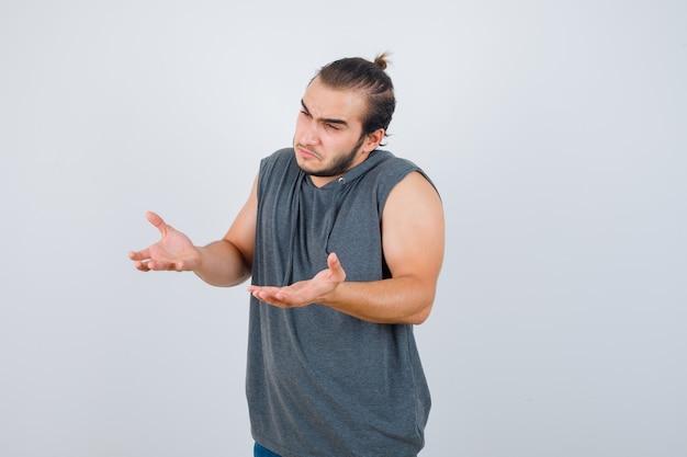 Junge passende männliche ausbreitungshandflächen in fragender weise in ärmellosem kapuzenpulli und nachdenklich aussehender vorderansicht.