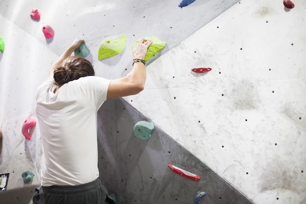 Junge passender männlicher kletterer, der sich auf felswand nach oben bewegt und drinnen auf künstlicher wand klettert.