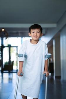 Junge patient, der mit krücken im korridor geht