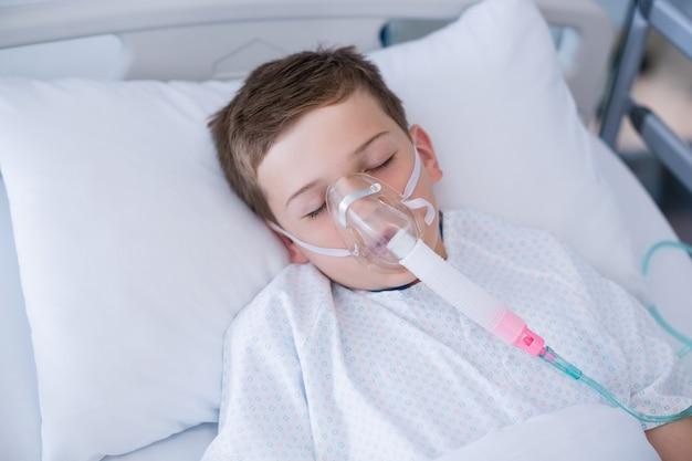 Junge patient, der sauerstoffmaske trägt, die auf krankenhausbett liegt