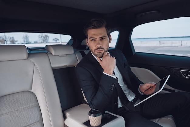 Junge perfektionistin. hübscher junger mann im vollen anzug, der mit digitalem tablet arbeitet, während er im auto sitzt