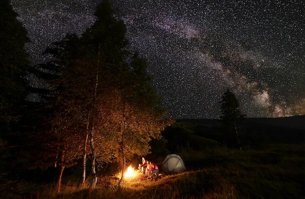 Junge person am lagerfeuer sitzt auf baumstämmen während des nachtcampings zwischen bäumen nahe dem zelt