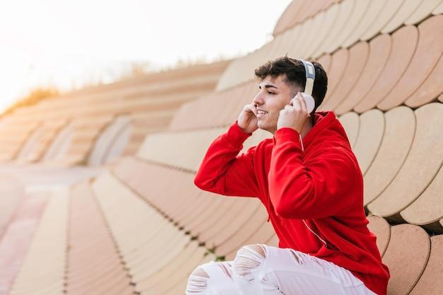 Junge person, die musik mit kopfhörern hört