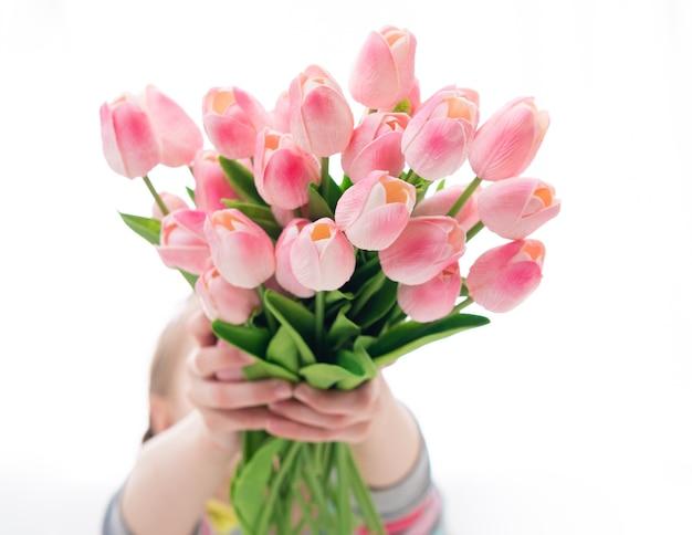 Junge person mit majestätischen strauß rosa tulpen auf weißem hintergrund