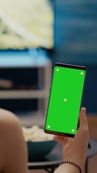 Junge person mit vertikaler greenscreen-anzeige auf dem smartphone
