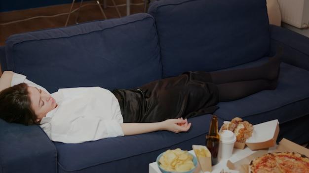 Junge person schläft auf der couch ein und lässt die tv-fernbedienung fallen