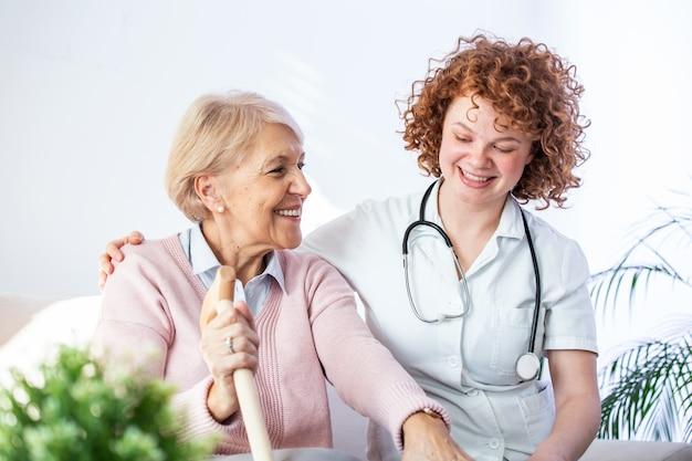 Junge pflegekraft und ältere frau, die zusammen beim sitzen auf sofa lachen.