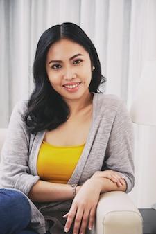 Junge philippinische frau, die auf couch sitzt