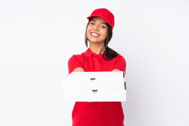 Junge pizza-lieferfrau über isolierte weiße wand, die imaginären copyspace auf der handfläche hält, um eine anzeige einzufügen