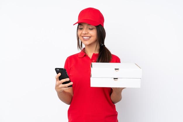 Junge pizza-lieferfrau über isolierte weiße wand, die kaffee hält, zum wegnehmen und ein handy