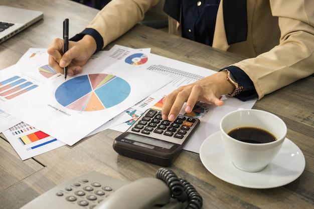 Junge plnning firma der geschäftsfrau durch datendiagramm und diagramm für managementgewinn und -finanzierung