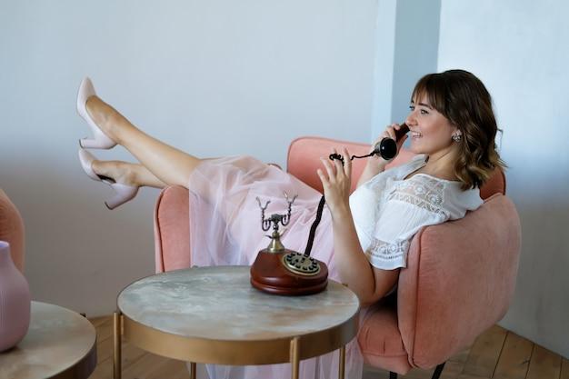 Junge plus die größenfrau, die an einem retro- telefon sitzt in einem stuhl spricht erstes datum, flirtend