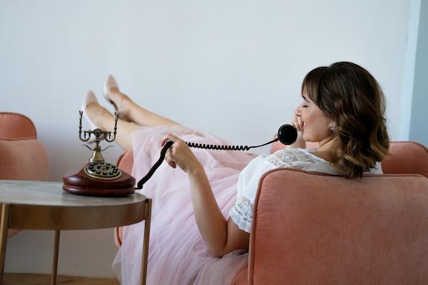Junge plus die größenfrau, die an einem retro- telefon sitzt in einem stuhl spricht