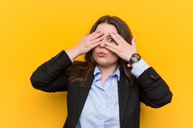 Junge plus größenkaukasier-geschäftsfraublinzeln durch die finger erschrocken und nervös.