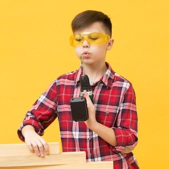 Junge posiert mit bohrmaschine
