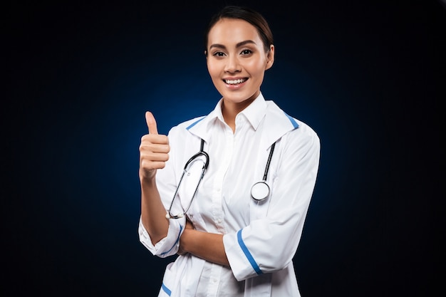 Junge positive ärztin mit dem stethoskop, das sich daumen zeigt