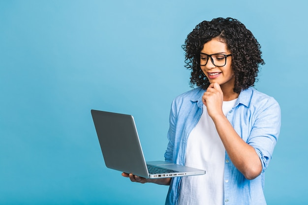 Junge positive afroamerikanerschwarze positive coole dame mit lockigem haar unter verwendung des laptops und des lächelns lokalisiert über blauem hintergrund.