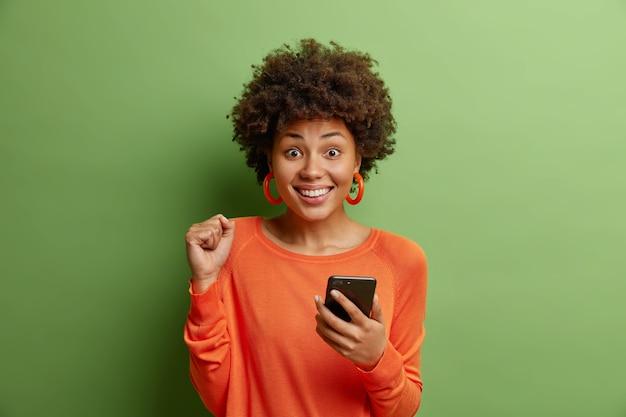 Junge positive afroamerikanische frau mit lockigem haar ballt faust liest nachricht am telefon gekleidet in lässigem orangefarbenem pullover, der über grüner wand isoliert wird, freut sich über gute nachrichten