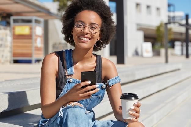 Junge positive dunkelhäutige teenager-nachrichten online, genießt kaffee zum mitnehmen aus einwegbechern, trägt zerlumpte jeansoveralls, genießt freizeit im freien. streetstyle. lifestyle-konzept.
