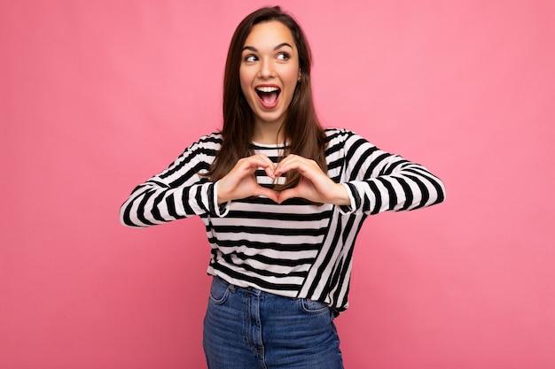 Junge positive entzückende glückliche nette brünette frau mit aufrichtigen emotionen, die einen lässigen gestreiften pullover einzeln auf rosafarbenem hintergrund mit leerem raum trägt und herzform mit den händen macht.