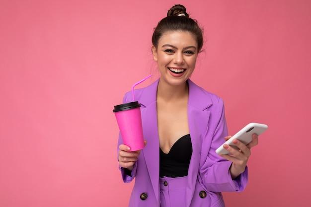 Junge positive frau isoliert über rosafarbenem hintergrund mit kopienraum, der kaffee zum mitnehmen und ein mobiltelefon hält