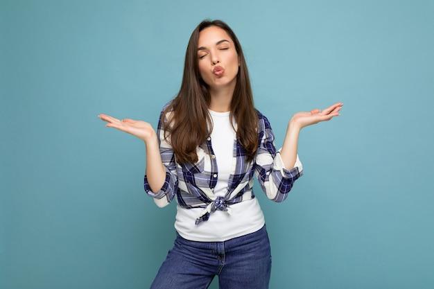 Junge positive glückliche schöne winsom brünette frau mit aufrichtigen emotionen, die ein kariertes hemd trägt, das auf blauem hintergrund mit kopienraum lokalisiert wird, der zwei hände zeigt und kuss gibt.