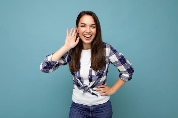 Junge positive schöne brunet-frau mit aufrichtigen emotionen, die ein trendiges karohemd trägt, das isoliert auf blauem hintergrund mit leerem raum steht und etwas hört, indem sie die hand auf das ohr legt