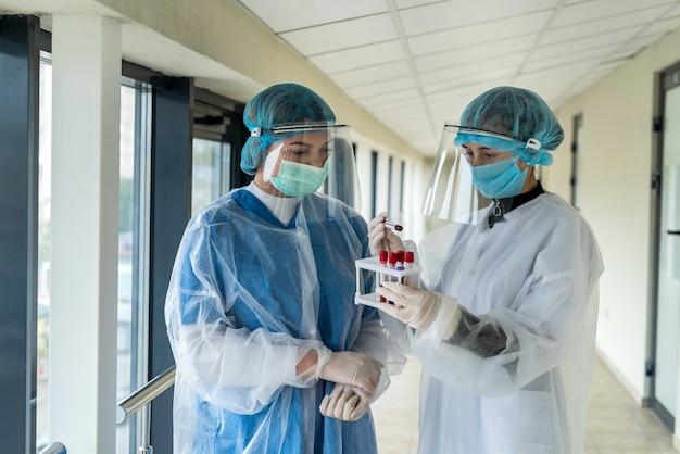 Junge praktikanten arbeiten mit reagenzgläsern mit blut für laboruntersuchungen, um ein neues gefährliches virus covid19 zu erkennen