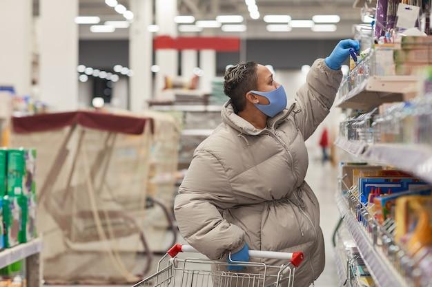 Junge pralle frau in der schutzmaske, die einkäufe im supermarkt während der pandemie kauft