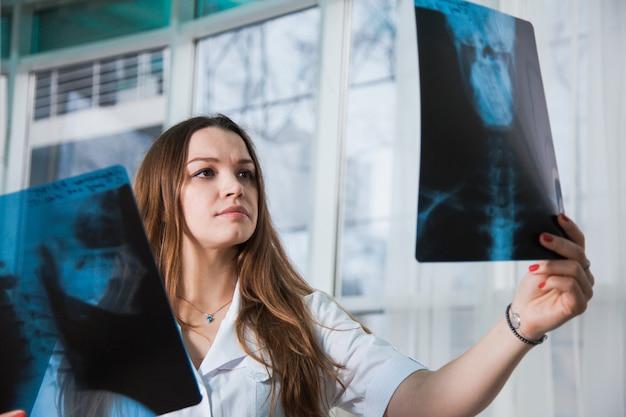 Junge professionelle ärztin, die das röntgenbild des menschlichen schädels des patienten während eines besuchs untersucht. gesundheitsmedizinisches konzept