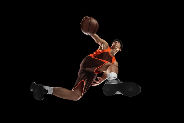 Junge professionelle basketballspieler in aktion, bewegung isoliert auf schwarzer wand, blick von unten. konzept von sport, bewegung, energie und dynamischem, gesundem lebensstil. trainieren, üben.